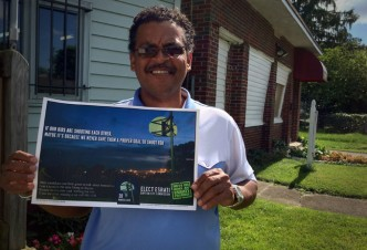 Dr. Alonzo Patterson holding an Elect Esrati poster