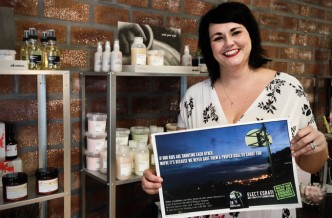 Tessa Hickey of one80salon in Dayton holding an Elect Esrati Hoops Dayton poster